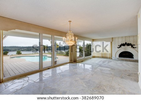 Large luxury outdated unfurnished living room with fireplace and marble floor. - stock photo
