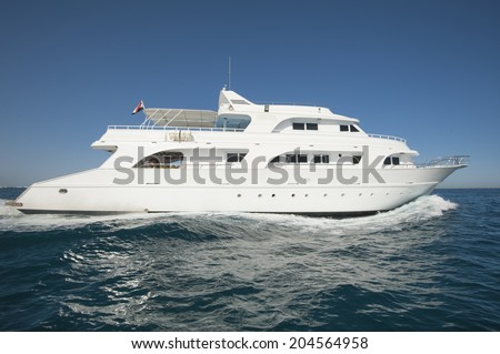 Large luxury private motor yacht out on tropical sea - stock photo