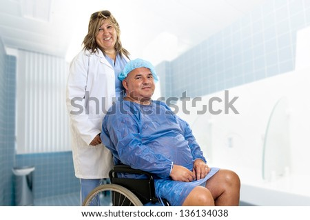 Large male patient in a wheelchair with doctor - stock photo