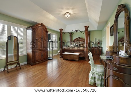 Large master bedroom with wood framed bed - stock photo