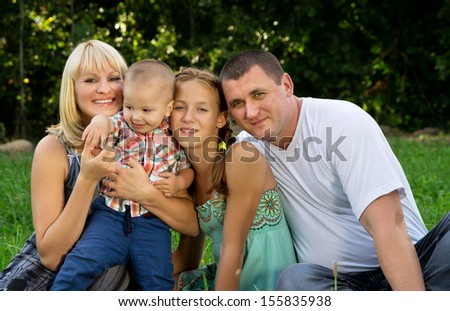 large merry family has a rest on the nature - stock photo