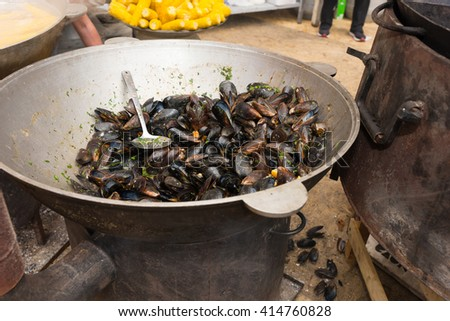 Large metal bowl of freshly cooked steamed saltwater mussels alongside a brazier or stove ready for serving at a catered outdoor event - stock photo