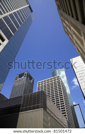Large modern buildings downtown, blue sky & white clouds