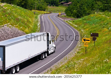 Large modern classic white truck with a trailer carrying commercial industrial cargo on the scenic highway winding among hills covered with trees and separated the safety barrier with road signs.