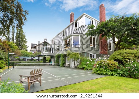 Large modern house with tennis court and patio area - stock photo