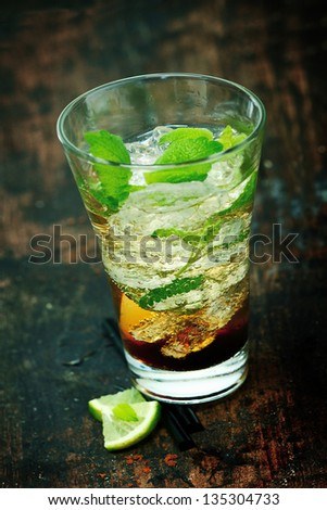 Large mojito rum cocktail with ice, rum, lime jiuce, and mint leaves standing on an old wooden bar counter
