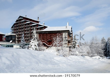 Large mountain cottage under heavy winter
