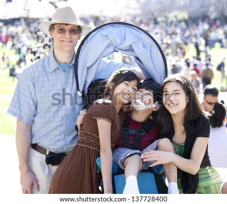 Large multiracial family in crowd with disabled child in wheelchair. Flowering cherry trees in background. - stock photo