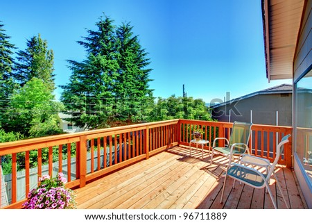 Large new wood deck home exterior with chairs, trees and flowers.