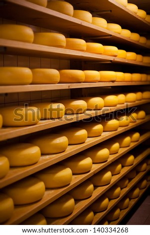 Large number of cheese-wheels aging on shelves at the cellar of the cheesemaker shop - stock photo