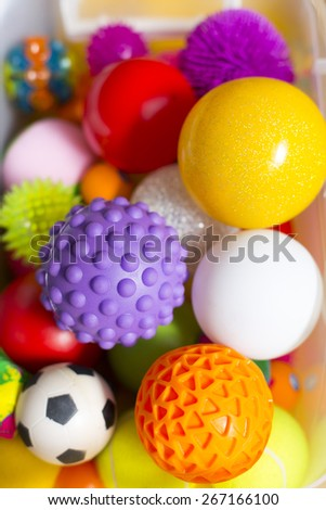 Large number of colorful plastic toy balls with different colors together in a basket, vertical composition - stock photo