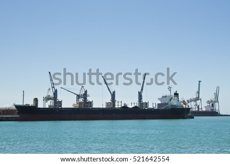 Large ocean cargo vessel in a harbor or port being off loaded