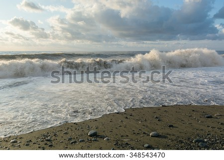 Large ocean waves breaking on the beach under a sky with clouds