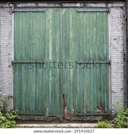 large old barn doors with peeling green paint in white brick wall