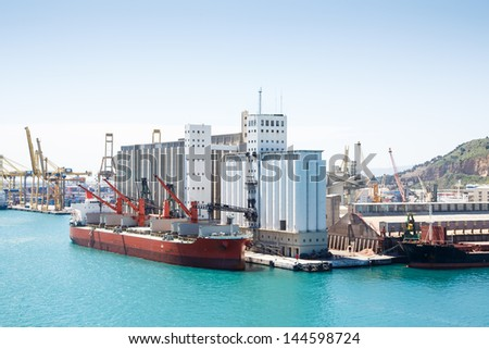 Large old freighters at an industrial shipping harbor in Barcelona, Spain - stock photo