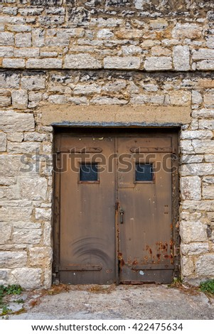 Large Old Metal Doors on Large Stone Building - stock photo