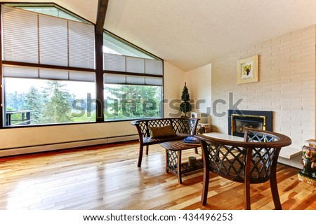 Large open living room with vaulted ceiling, white brick fireplace and hardwood floor.