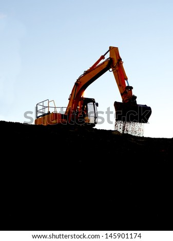 Large, orange bulldozer on ridge line dropping soil from bucket