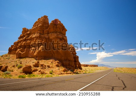 Large orange rock sandstone formation in the desert of Utah stings high beside the black asphalt highway. - stock photo