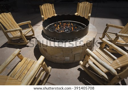 Large outdoor fire pit surrounded by wooden rocking chairs - stock photo