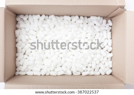 Large packaging box filled with many white styrofoam pellets