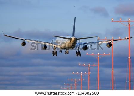Large passenger airplane approaching runway - stock photo