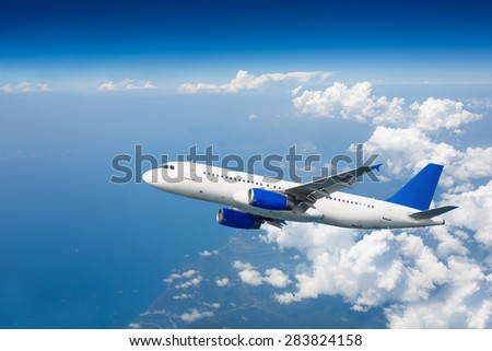 Large passenger airplane flying over clouds in blue sky. Travel airline concept