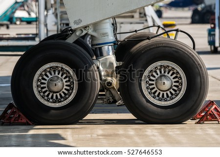 Large passenger airplane maintenance personnel working on aircraft main landing gear repair detail exterior close up view.