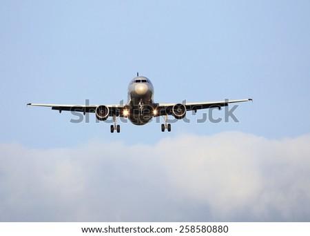 Large passenger jet plane during descent just before landing - stock photo
