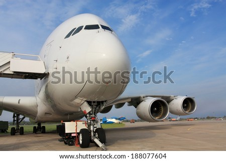 Large passenger jet  with attached ladder, front view - stock photo