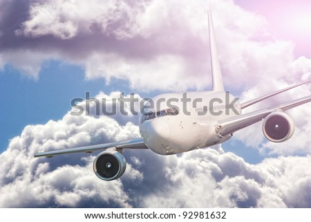 Large passenger plane flying in the blue sky - stock photo