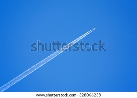 Large passenger supersonic plane flying high in clear blue sky, leaving long white trail - stock photo