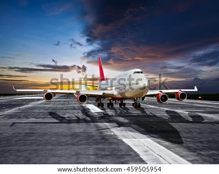 Large passenger wide-body airplane before take-off. Aircraft runs along the airport runway during the sunset time. - stock photo