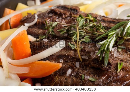 Large piece of fresh beef meat prepared on a grill pan with herbs and vegetables. Shallow depth of field. - stock photo