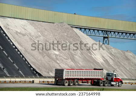 Large Piles of Road Salt Being Loaded on Semi Truck - stock photo