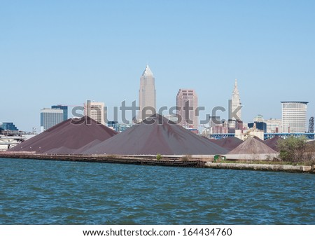 Large piles of taconite and other aggregate materials at the Cleveland Bulk Terminal on the shore of Lake Erie with downtown Cleveland, Ohio in the background