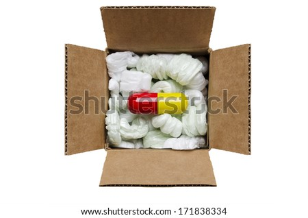 Large pill in a box with packaging peanuts  - stock photo