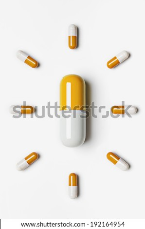 Large pill surrounded by small pills - stock photo