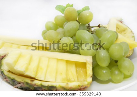 large plate of sliced fruit on white background