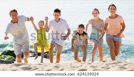 Large positive family of six people running together on beach on sunny day