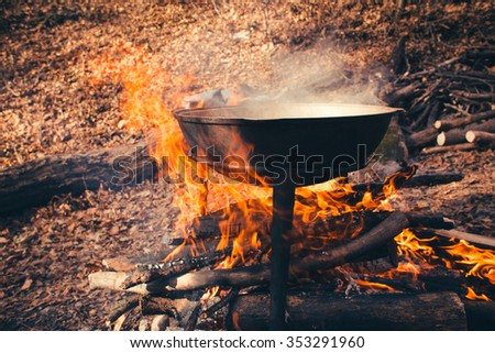 Large pot over a campfire cooking in cast-iron cauldron in nature. - stock photo