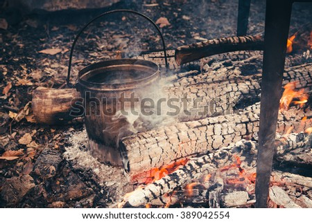 Large pot over a campfire cooking in cast-iron cauldron in nature. Food, Camping, cooking over a fire in the boiler - stock photo