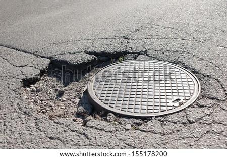Large pothole in asphalt and circular manhole cover of sewage well in road, close metal sewer cover in Warsaw, Poland, horizontal orientation, nobody. - stock photo