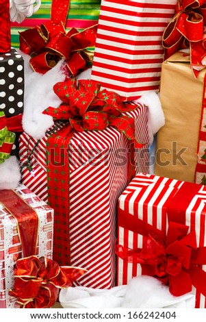 Large presents wrapped in colorful papers with bows in a pile ready for Christmas.