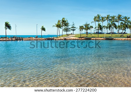 Large public pool located next to the sea in tropical resort - stock photo