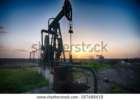 Large pump jack pumping crude oil up to the surface. - stock photo