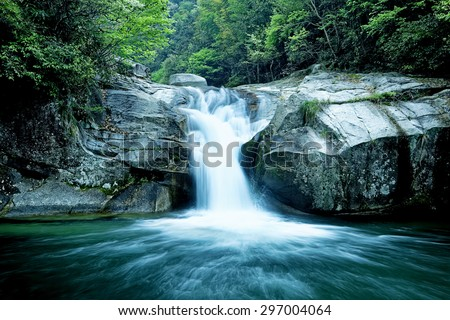 Large rain forest waterfall, sun beams, and mossy rocks - stock photo