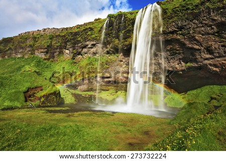 Large rainbow decorates a drop of water. Seljalandsfoss waterfall in Iceland. Summer sunny day  - stock photo