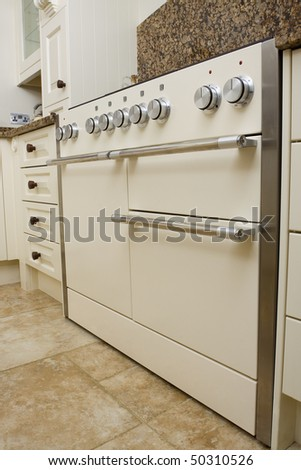 Large range style cooker in modern kitchen interior with granite worktop and cream units - stock photo