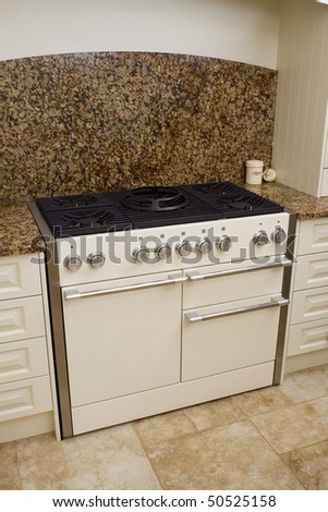 Large range style cooker in modern kitchen interior with granite worktop and cream units